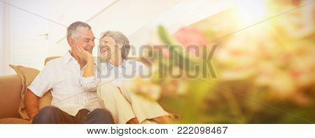 Loving senior couple relaxing on sofa at home