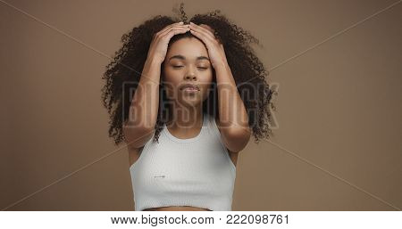 mixed race black woman portrait with big afro hair, curly hair in beige background touching hair