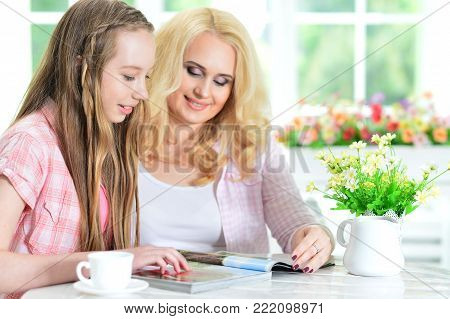 mother and daughter sitting at table and reading magazine