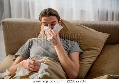 Poor fellow. Waist up portrait of tired guy who is terribly ill. He is lying in bed and holding a glass of water while blowing his nose