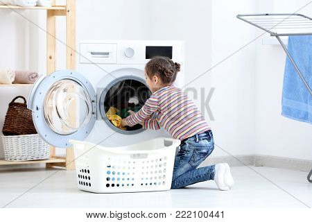 Cute little girl doing laundry at home