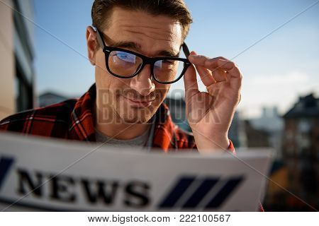 Close up portrait of calm guy holding the newspaper in the hand outdoor, focus on his face while he is looking at camera with rapt gaze