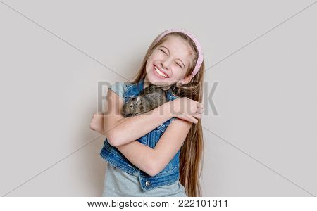 Smiling little girl holding a degu on her arms