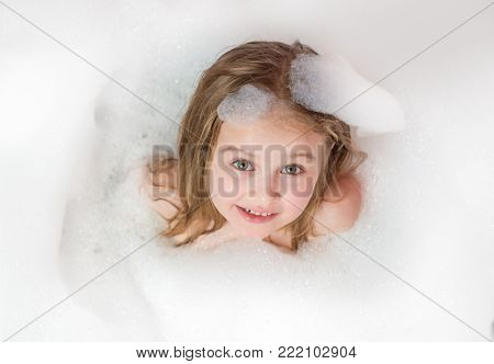 Little girl bathes in a bath with foam and bubbles