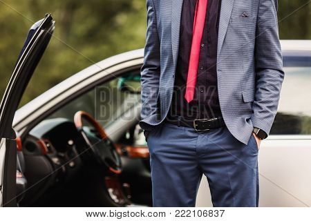 Luxury business man in a dark business suit near car. Success in the difficult task. Luxury business man in a dark suit. Luxury man. Luxury in business. Achieve luxury in work. The man enjoys luxury.Fashionable watch on hand. Hand in pocket