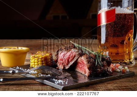 Grilled tenderloin Steak roastbeef and mushrooms sauce on black cutting board and glass of beer on wooden table. Serving a ready meal in a restaurant, cafe, bar, pub. Still life. Copy space. dry aging, marbled beef, fillet mignon, Chateaubriand, Ribey
