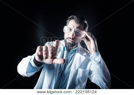 Sensory technology. Selective focus of a scientists hand touching a sensory screen while standing against black background