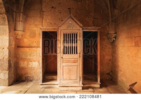 ORADOUR SUR GLANE, FRANCE - December 03, 2017 : inside the church where were burned women and children during the massacre of the population by the Nazis on June 10, 1944, the wooden confessional retained almost intact since that time