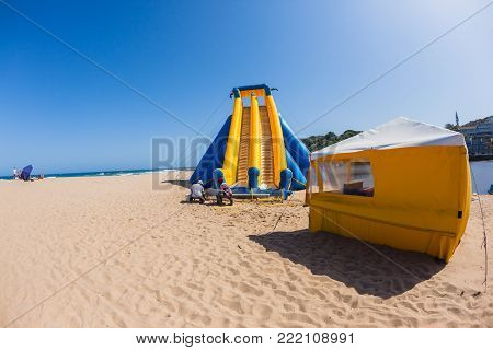 Beach action thrill jump ride down high inflatable water slide summer holidays landscape.