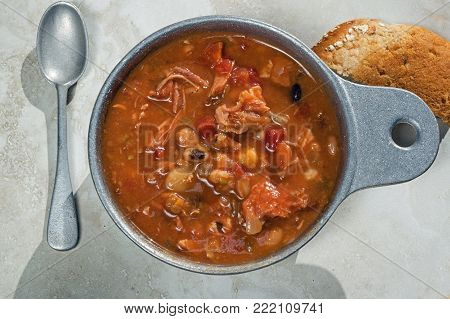 Smoked turkey meat and bean soup in metal soup bowl. It is a classic soup recipe and includes smoked turkey, tomato, celery and onion.
