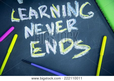 Education concept: Learning Never Ends inscribed with colored chalks on a black chalkboard and pencils, top view