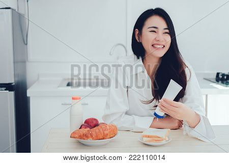 Asian woman making bread with sweetened condensed milk ,sweet spiced milk in the morning and eating apple fruit healthy food breakfast meal in kitchen room fresh start the day at home