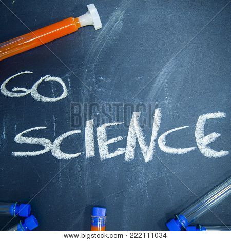 Education concept: Go Science inscribed with colored chalks on a black chalkboard and chemistry flasks, top view, close up, square crop