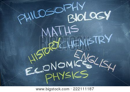 Education concept: Names of school subjects inscribed on a black chalkboard with colored chalks