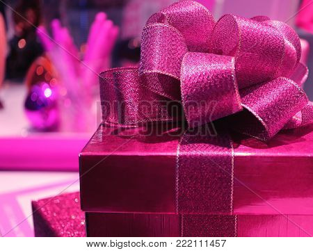 Closed up a square shiny vivid pink gift box with gritter vivid pink ribbon bow, selective focus, blurred background