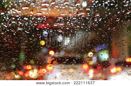 Blurred street lights and tail lamps viewed through water droplets on car windshield, for background or banner