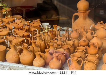 Handmade souvenir clay vases, jugs and pots in window of tourist resort store. Resort classic Greek sculpture in port-city Rethymno. Crete, Greece
