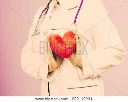 Help people concept. Medical idea of helping. Part body female doctor cardiologist with red heart enjoy her work. Woman wearing medic apron. Filtered.
