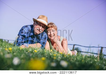 Senior couple laying on the grassfield, smiling. Happy mature couple.