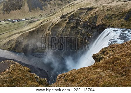 Amazing waterfall falls down from the cliff into the valley in Iceland. Cliff covered by faded grass. River flowing into the valley with small settlement. Horizontal.