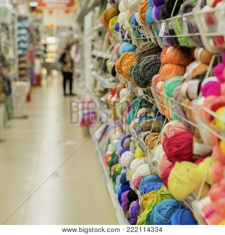 Woman makes choosing yarn for knitting in the store of goods for creativity and needlework. Shelves in needlework store. Abstract defocused motion blurred. For background, backdrop