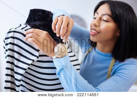 Necessary pins. Qualified responsible young tailor taking a pin from a tiny pin cushion on her wrist while working on a new order