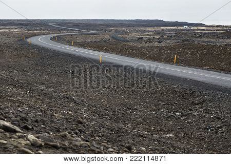 Deserted roadway with orange roadside pillars between the rocky terrain on the background of the sky and the sea in Iceland. Horizontal.