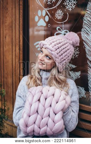 Young blonde woman in smoky pink knitted hat, knitted neck warmer and blue jeans make posing on a wooden bench  with christmas cafe-window on background