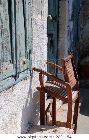 A wooden folding chair against awall in Kastellorizo Greece poster