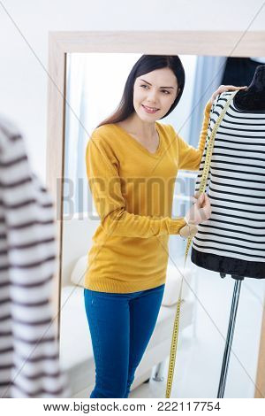 Checking length. Smart skilled young tailor looking satisfied while looking at the ready striped blouse and checking the length of its sleeve