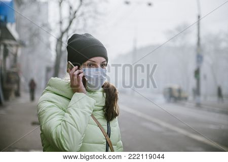 a woman stands near a road in the city in a protective medical mask. Protection from viruses in the city. A woman is ringing on the street in a medical mask.