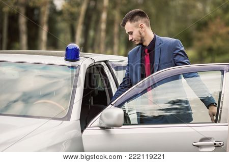 Successful business man in a dark business suit in the car. Stylish man in car. Young driver in car. Sitting behind the wheel of a new car. A man is smiling in the car. To drive car