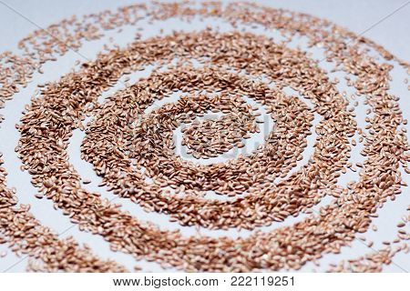Organic food concept with flax seeds on a gray background, close up.