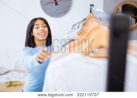 Touching clothes. Cheerful young worker of a popular atelier standing near the clothes rail and trying to get some items from it