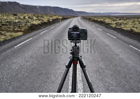 Black camera on the tripod on the roadway with orange roadside pillars between the green fields and mountains on the background of the sea and cloudy sky in Iceland. Closeup. Horizontal.