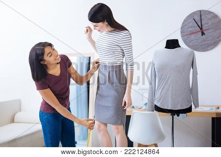 Appropriate length. Emotional young hardworking tailor standing with a tape measure and feeling satisfied with the length of a new beautiful dress