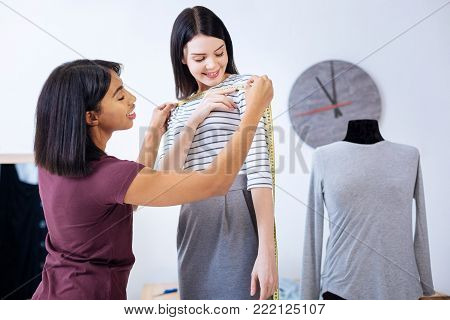 Helpful client. Cheerful skilled tailor doing all the necessary measurements while her calm attentive curious client smiling and pressing the tape measurer