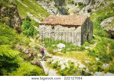 PICOS DE EUROPE, SPAIN - JULY 9, 2016: The ancient stone shed with a tile roof in mountains. The man with a backpack, the tourist, approaches the shed in sunny summer day. Soft focus