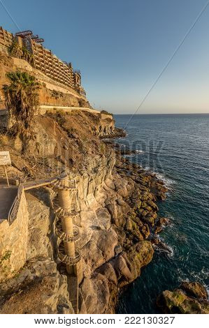 Puerto Rico, Gran Canaria Spain December 2017 The beautiful promenade connecting Puerto Rico and Amadores. A spiral staircase leading down to the sea. Gloria Palace Hotel at the top of the mountain.