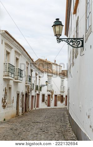 European touristic small town Faro, Portugal. Traditional historic old city architecture, white walls of houses, a lantern on the wall