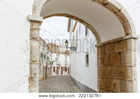 European touristic small town Faro, Portugal. Traditional historic old city architecture, white walls of houses, a lantern on the wall. View through the arch