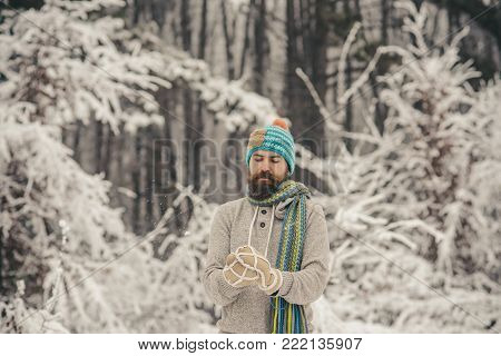 Hand With Snowball In Mitten Of Blurred Bearded Hipster