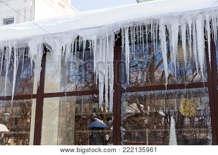 Icicles Hang Over The Window Of The Old Cafe. Snowdrifts In The City On A Winter Frosty Day, Snowfal