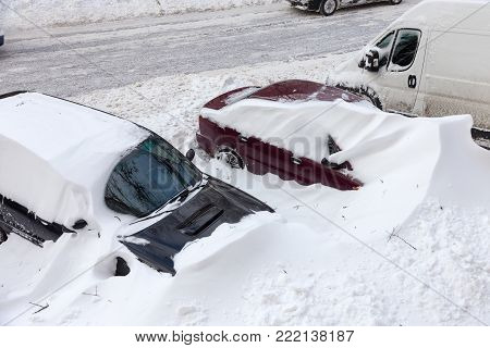 Snow drifts in the city on a winter frosty day. Car blocked in the yard by snowdrifts after the heavy snow storm Snow drifts in the city on a winter frosty day. Car blocked in the yard by snowdrifts after the heavy snow storm