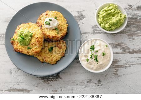 healthy vegetable rosti from cauliflower and parmesan cheese with dips from sour cream and avocado, parsley garnish, blue plate on a bright rustic wooden table with copy space, high angle view from above