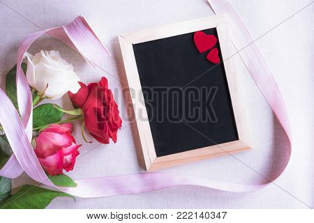 Chalkboard with red hearts and roses - Valentine day theme image with beautiful roses tied with pink ribbon and a blank chalkboard decorated with two red hearts.