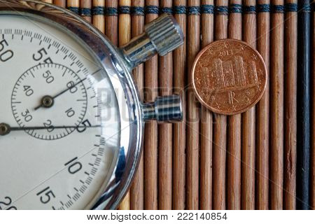 Euro coin with a denomination of 1 euro cents and stopwatch on wooden table - back side