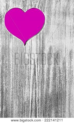 Pink heart carved in a wooden board. Background