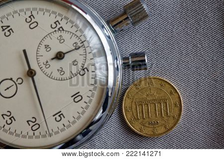 Euro coin with a denomination of 10 euro cents (back side) and stopwatch on gray denim backdrop - business background