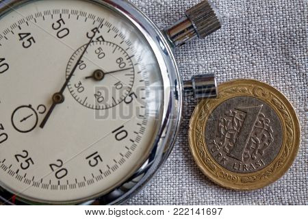 Turkish Coin With A Denomination Of One Lira And Stopwatch On Gray Flax Backdrop - Business Backgrou